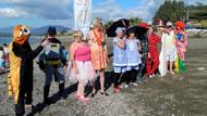 Turistler kostümle denize girip yardım topladı