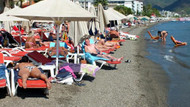 Bikinili turistleri buzlu suyla serinleten garson