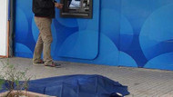 Yerdeki cenazeye rağmen ATM'den para çektiler
