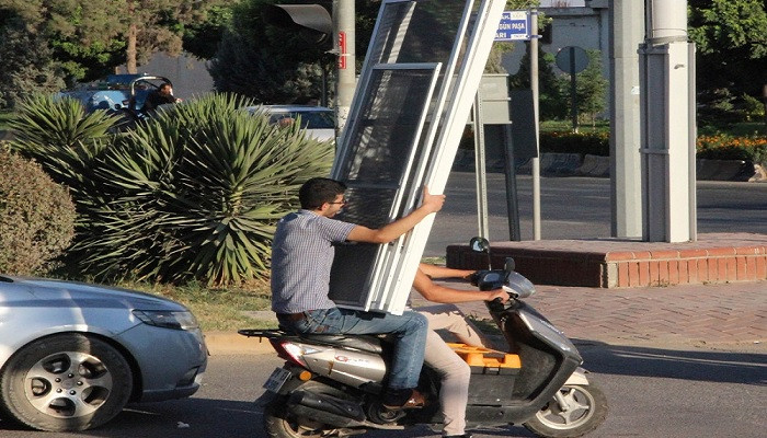 Motosikletle kapı taşıyan ikili pes dedirtti